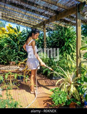 Jeune femme d'arroser les plantes, chambre terrasse, jardin tropical, Guadeloupe, French West Indies, Banque D'Images
