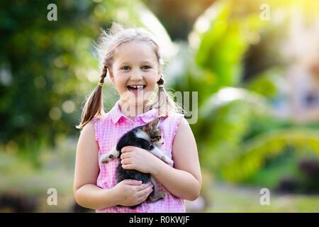 Enfant tenant bébé chat. Des enfants et des animaux de compagnie. Little girl hugging mignon petit chaton au jardin d'été. Animal domestique dans les familles avec enfants. Les enfants atteints d'hom Banque D'Images