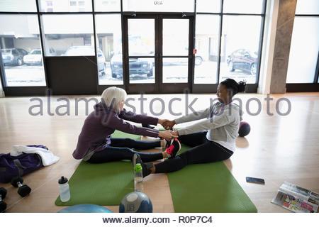 Les femmes s'étendant les bras, dans l'exercice de fitness studio Banque D'Images