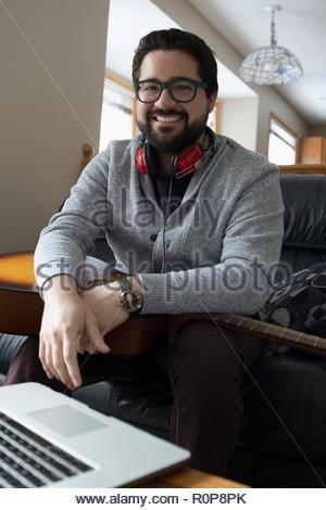 Portrait smiling Latinx man with guitar at laptop Banque D'Images