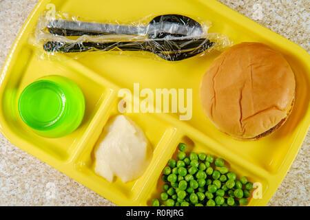 Déjeuner à l'école élémentaire cheeseburger avec de la purée de pommes de terre et les pois verts gélatine partie sur le bac Banque D'Images