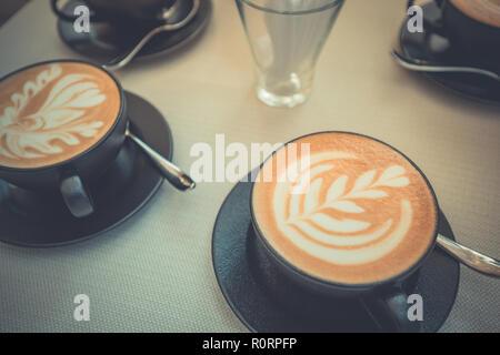 Latte art chaud dans une tasse sur la table en bois et un café avec l'arrière-plan flou flou de l'image. Latte art table basse vue d'en haut, heureux de l'humeur de détente Banque D'Images