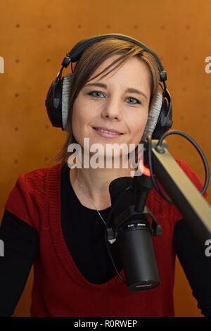 Journaliste Femme portant des écouteurs et à l'aide d'un micro pour présenter à la radio Banque D'Images