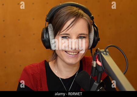 Journaliste Femme portant des écouteurs et à l'aide d'un micro pour parler à la radio Banque D'Images