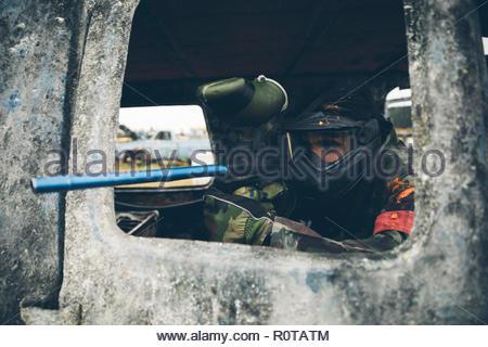 L'homme en voiture rouillée paintball Banque D'Images