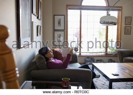 Latinx senior woman reading book on salon canapé Banque D'Images