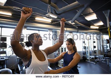 Personal trainer helping woman en utilisant l'équipement d'exercice dans la salle de sport Banque D'Images