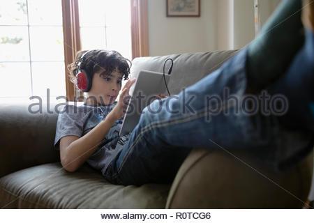 Garçon Latinx avec casques using digital tablet on sofa Banque D'Images