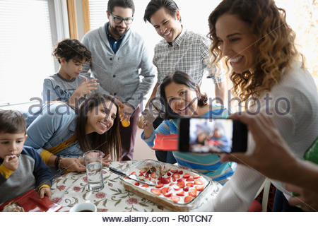 Man with camera phone photographier Latinx multi-generation family celebrating birthday avec gâteau Banque D'Images