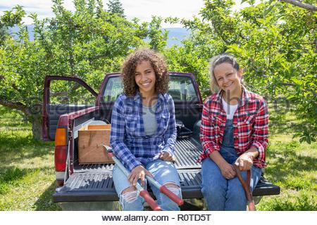 Portrait souriant, confiant les agricultrices assis à l'arrière du camion dans Orchard Banque D'Images