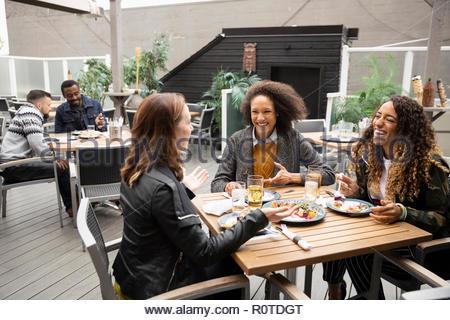 Les amis des femmes appréciant le déjeuner sur patio cafe Banque D'Images