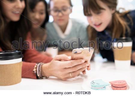 Mères et filles à l'aide de smart phone et boire du café en café Banque D'Images
