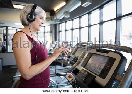 Senior woman avec des écouteurs et un lecteur mp3, d'écouter de la musique sur tapis roulant dans une salle de sport Banque D'Images
