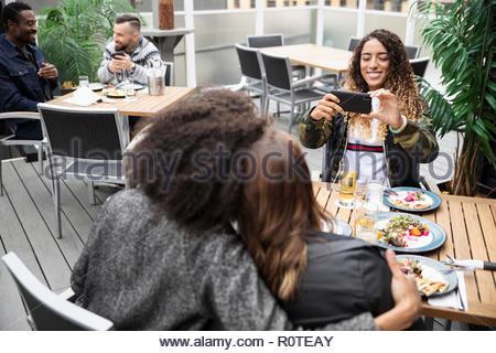Femme avec smart phone photographier friends hugging sur patio cafe Banque D'Images