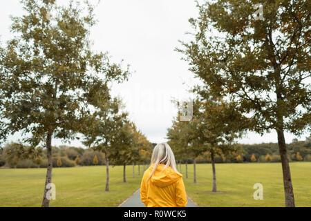 Blonde woman walking in park