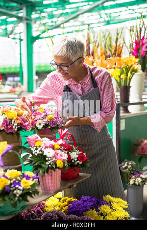 Charrming senior woman organise des fleurs sur le marché local Banque D'Images