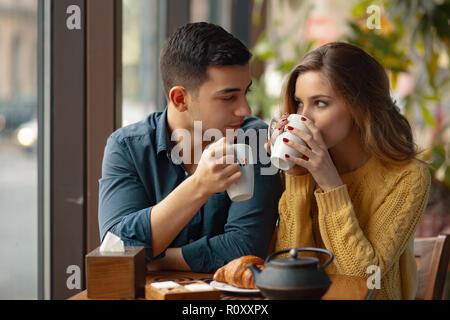 Jeune beau couple sur date dans un café ayant une conversation et d'apprécier le temps passé avec l'autre. Banque D'Images