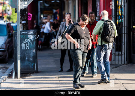 New Orleans, USA - 22 Avril 2018: trottoir de la rue des Français en Louisiane ville, ville, immeuble, happy smiling woman tourist, coucher de soleil coloré Banque D'Images