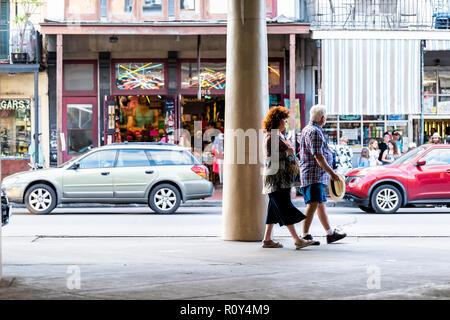 New Orleans, USA - 22 Avril 2018: vieille ville Decatur Street en Louisiane célèbre ville, deux personnes marchant par les magasins boutiques dans coucher soleil soir Banque D'Images