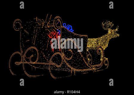 Éclairage de Noël d'un traîneau de rennes avec cadeaux comptable dans un jardin à l'extérieur