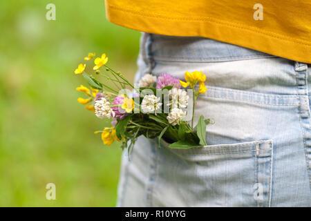 Fleurs sauvages dans la poche de jean bleu Banque D'Images