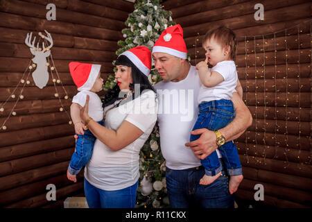 La famille près de l'arbre de Noël. Les parents ayant des enfants à l'arbre. Nouvelle année, moment magique. Joyeux Noël Banque D'Images