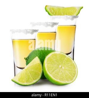 Trois verres de tequila dorée avec stand de chaux entières et tranchées Banque D'Images