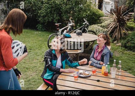 Trois adultes femelles matures réunion jusqu'à prendre des rafraîchissements dans un parc après une balade à vélo. Banque D'Images