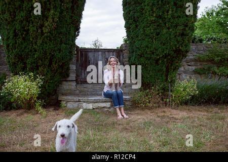 Femme mature avec deux chiens assis dans jardin, portrait Banque D'Images
