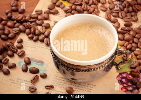 Une photo de café dans une tasse vintage, avec des grains de café, sur un vieux papier journal, tonique libre