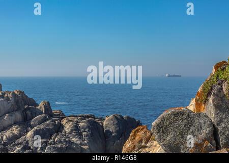 Vue sur l'océan atlantique avec des navires, ciel et mer en fond sonore et les rochers sur la côte de Leca da Palmeira, Porto, Portugal Banque D'Images