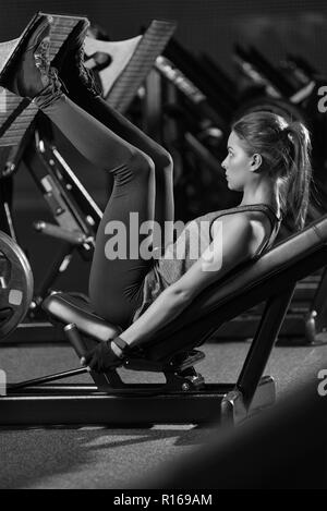 Femme sportive à l'aide de poids Appuyez sur la machine pour les jambes. Une salle de sport. Banque D'Images