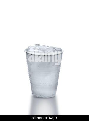 Tasse en plastique plein d'eau glacée contre fond blanc Banque D'Images