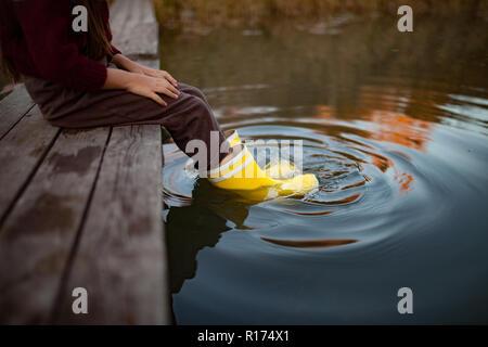 Dans l'enfant bottes en caoutchouc jaune se trouve sur pont en bois et met ses jambes dans l'eau sur fond de rivière. Libre.