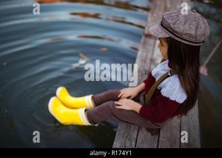 Enfant fille en bottes en caoutchouc jaune et le siège au pont de bois et met ses jambes dans l'eau sur fond de rivière.