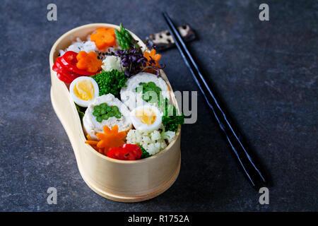 Boîte bento japonais avec du poulet farci aux asperges, riz, légumes et oeufs de caille Banque D'Images