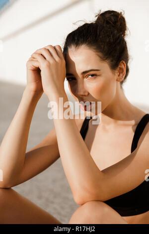 Image de l'incroyable jeune femme assise sur un tapis de sport en plein air sur la plage. Banque D'Images