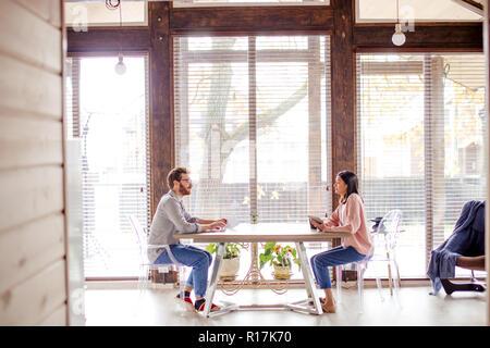 Un homme et une femme sont assis à une table en face de l'autre.