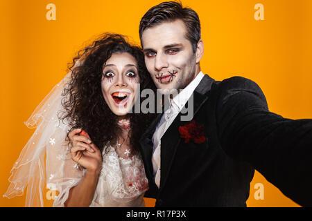 Photo de couple marié et zombie amusant bride wearing wedding outfit et rire maquillage Halloween tout en tenant plus isolés selfies retour jaune