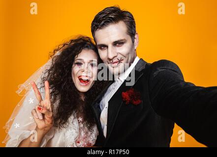 Photo de beau couple marié mariée zombie et portant des vêtements de mariage et maquillage halloween riant tout en tenant sur jaune isolé selfies ba