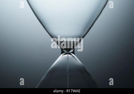 Vue rapprochée de l'écoulement de sable blanc par hourglass contemporain, fond uni Banque D'Images
