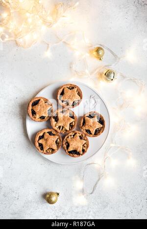 Petits pâtés pour Noël sur fond blanc avec la lumière, l'espace de copie. Le dessert traditionnel de Noël - petits pâtés. Banque D'Images