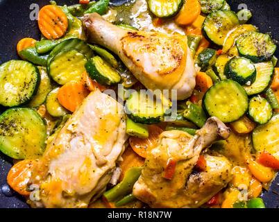 Poulet frit avec des légumes dans une poêle. Les cuisses de poulet avec un barbecue et des légumes près de l'arrière-plan. Banque D'Images
