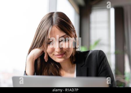 Jeune femme regarde dans l'écran de l'ordinateur portable. Les blogs de fille, la navigation sur internet, à discuter. Assis dans un café avec grande fenêtre Banque D'Images