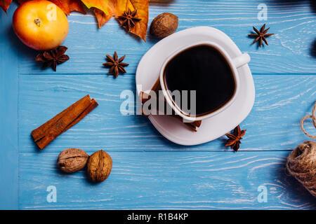 Café noir dans une tasse blanche sur une soucoupe avec de la cannelle et anis noyer sur une surface bleu apple Banque D'Images