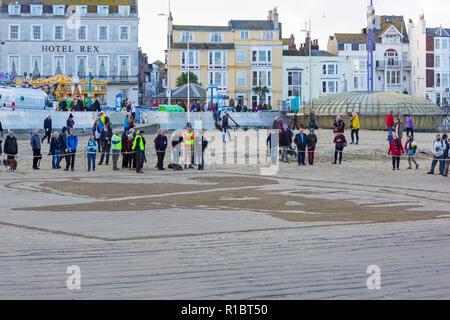 Weymouth, Dorset, UK. 11Th Nov 2018. Les collectivités de tout le Royaume-Uni se rassemblent sur les plages à 100 ans depuis l'armistice et la fin de la Première Guerre mondiale; pour vous dire merci et au revoir aux millions d'hommes et de femmes qui ont quitté leurs côtes pendant la guerre, beaucoup pour ne jamais revenir. Danny Boyle's Pages uniques de la mer où un portrait d'un individu à partir de la première WW1 se dégage de l'autruche et puis, quand la marée monte, c'est lavé. Credit: Carolyn Jenkins/Alamy Live News Banque D'Images