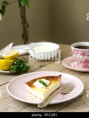 Petit-déjeuner sain à base de fromage blanc doux cocotte au gruau et le zeste de citron, servi avec de la crème, la menthe et le thé. Focus sélectif. Banque D'Images