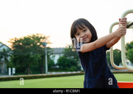 Smiling Little Girl s'amuser sur l'aire de jeux. Banque D'Images