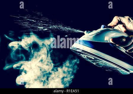 Côté est titulaire d'un fer à repasser à la vapeur et d'eau isolé sur un fond noir. Vintage, grunge, vieux, style retro photo. Banque D'Images