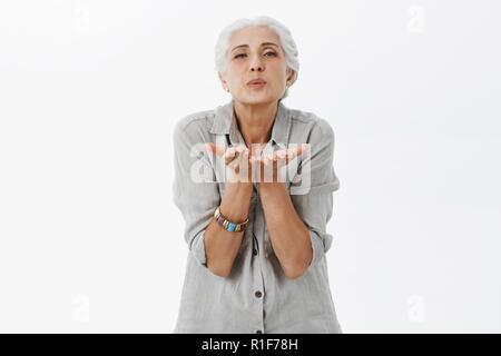 Taille plan sur genre et mignon aimer grand-mère aux cheveux gris lèvres pliage blowing kiss via air avec des palmiers près de la bouche de son mari aimant encore confesser dans l'affection et de tendres sentiments Banque D'Images